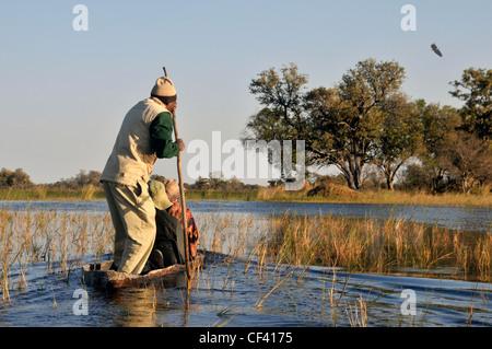 Makoro and poler on the Okavango river - Stock Photo