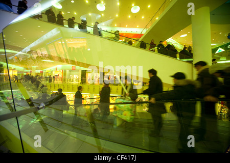 Escalator with buyers in shopping centre through yellow glass protection - Stock Photo