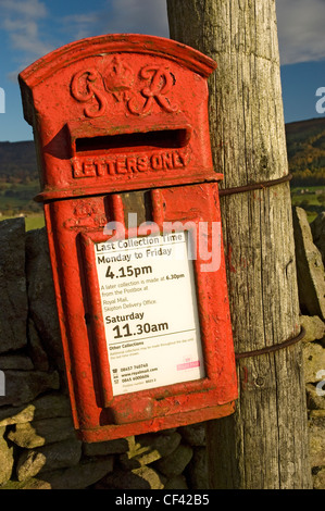 Old letterbox on a wooden post. - Stock Photo
