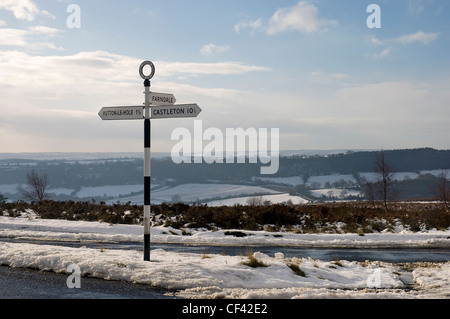 Snow surrounds a signpost next to a road on the North York Moors. - Stock Photo