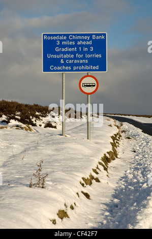 A warning sign beside the road to Rosedale Chimney Bank in winter. - Stock Photo