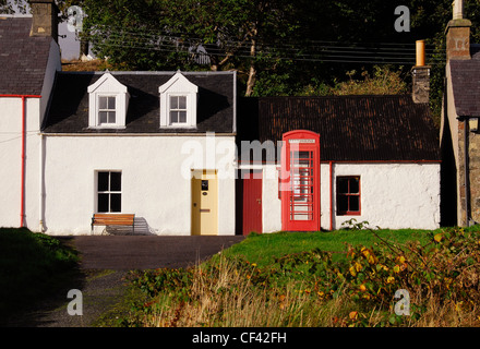 Red telephone box with cottages in the village of Plockton. The village has National Trust conservation status. - Stock Photo