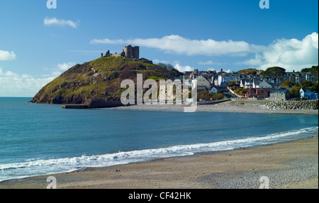 View across a deserted beach towards the ruin of Criccieth castle towering over Tremadog Bay. - Stock Photo