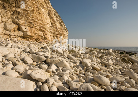 The rocky beach and sand coloured cliffs at South Landing in East Yorkshire. - Stock Photo