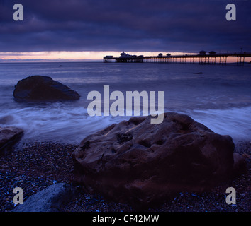 View over large boulders on the seashore towards Llandudno Pier at dusk. - Stock Photo