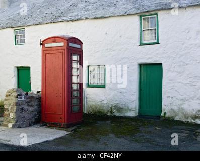 A public telephone box outside a remote farmhouse, previously a sub post office in Maenaddwyn. - Stock Photo