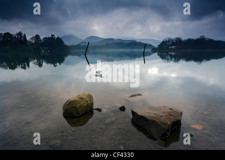 A layer of mist hovers above Lake Derwent as early morning daylight filters through a cloudy sky. - Stock Photo