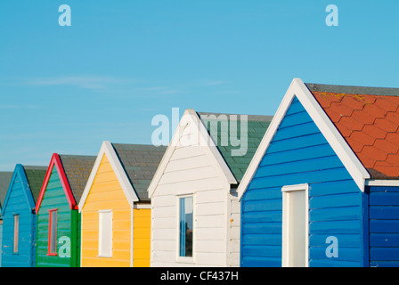Colourful beach huts. There is something quintessentially British about sitting outside what is essentially, a shed, - Stock Photo