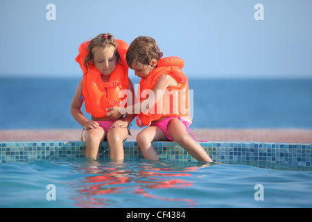 two little girls in lifejackets sitting on ledge pool on resort - Stock Photo