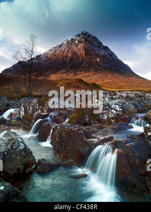 Water flowing over rocks in Glen Etive downstream from Buachaille Etive Mor, an almost perfect pyramidal form mountain - Stock Photo