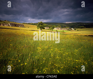 View across a hay meadow towards a village in the countryside surrounding Halifax. - Stock Photo