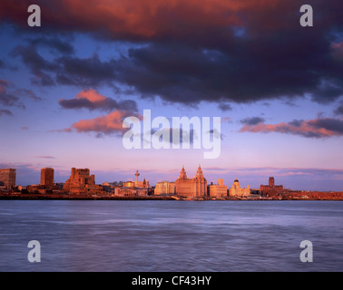 View across the River Mersey towards the Three Graces on the Liverpool waterfront at sunset. - Stock Photo