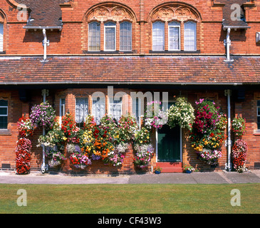 Flower baskets outside cottages in Port Sunlight. The houses were originally built for employees of Lever Brothers, - Stock Photo