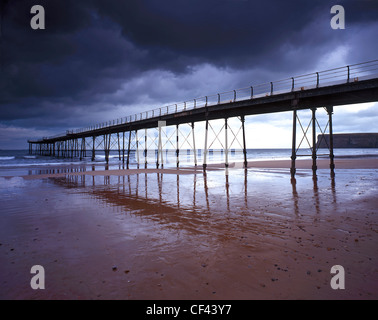 Saltburn Pier, the last pier remaining in Yorkshire, at low tide as storm clouds gather overhead. - Stock Photo