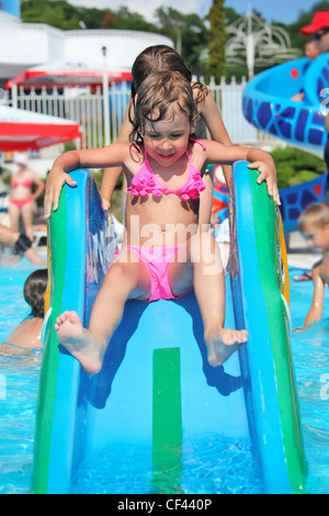 pretty little girl goes down on hill in aquapark of an entertaining complex - Stock Photo
