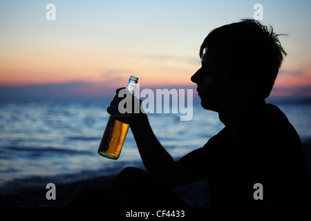 Silhouette teenager boy with beer bottler on stone seacoast in evening - Stock Photo