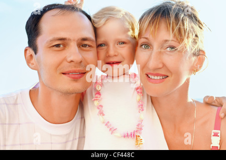 Happy family with little girl near to sea, concerning with heads - Stock Photo