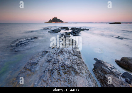 St Michaels Mount viewed from the exposed rocky foreground at low tide. - Stock Photo