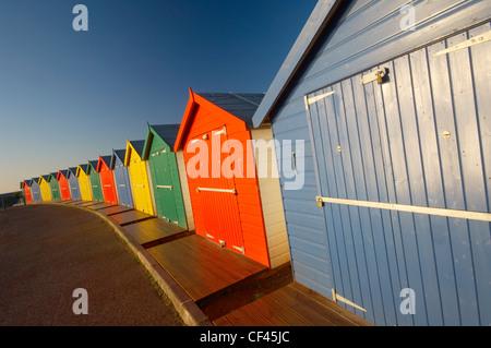 Bright multi coloured beach huts along Dawlish seafront at dawn. - Stock Photo
