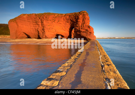The bright red Langstone Rock on Dawlish seafront viewed from the breakwater. - Stock Photo
