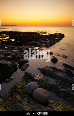 Sunset over the rocky beach at Abbotsham on the North Devon coast. - Stock Photo