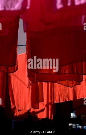 Freshly red dyed fabric hanging out to dry in Djemaa el-Fna market in Marrakech Morocco - Stock Photo
