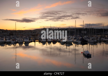 Dusk over luxury yachts in Brixham Marina. - Stock Photo