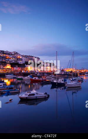 Boats moored in Brixham harbour at dusk. - Stock Photo