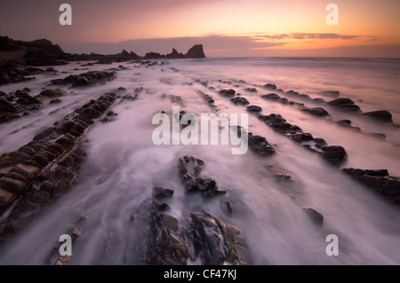 Sunset over rough seas washing in over jagged rocks on the foreshore of Hartland Quay in North Devon. - Stock Photo