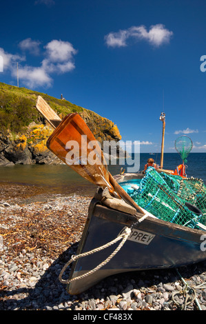 A fisherman working on his small fishing boat on the beach in Cadgwith Cove in Cornwall. - Stock Photo
