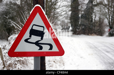 A rural slippery road sign with a snow covered road in the background in Essex. - Stock Photo
