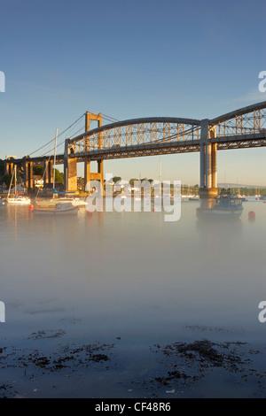 Dawn mist on the River Tamar below The Royal Albert Bridge and Tamar Bridge at Plymouth. - Stock Photo