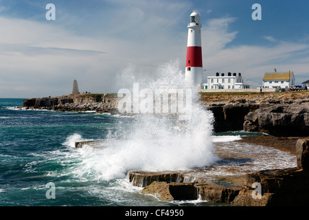 Waves breaking over rocks by Portland Bill lighthouse. - Stock Photo