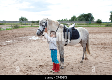 Little girl petting and standing next to her horse ready for a horseback riding lesson. - Stock Photo