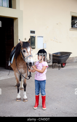 Little girl standing next to her horse ready for a horseback riding lesson. - Stock Photo