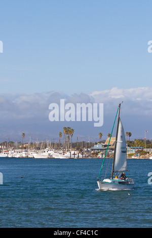 A sailboat heading out of the Channel Islands Harbor in Oxnard California - Stock Photo