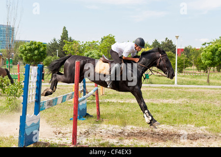 Jockey on black horse jumping in a public jump show. - Stock Photo