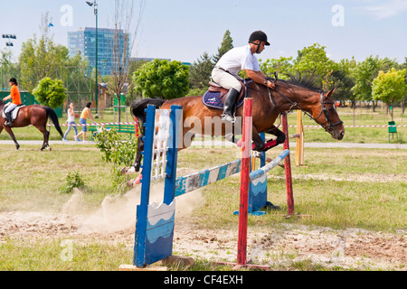 Jockey on horse jumping over an obstacle in a public jump show. - Stock Photo
