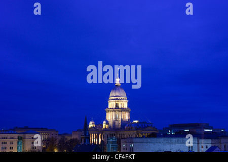 The Illinois State Capital building dome is lit up against a twilight blue sky in Springfield, IL. - Stock Photo