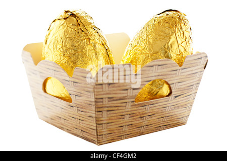Two gold foil chocolate Easer Eggs in a cardboard punnet - Stock Photo