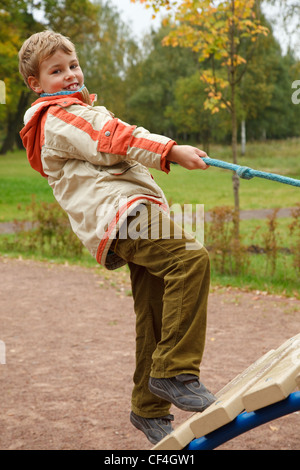 Boy in jacket is on playground in autumn park. Smiling, he climbs the stairs holding onto a rope. - Stock Photo