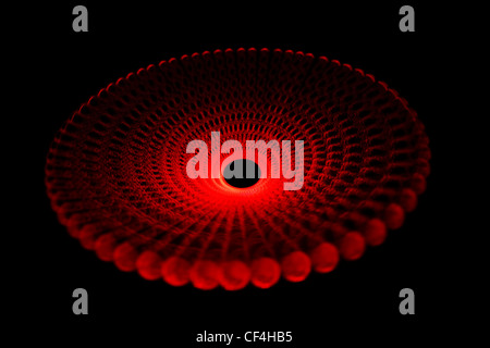 Glowing red light traces in form of disc on black background. Isolated. - Stock Photo