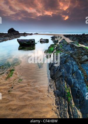 Rock formations and pools of water on Sandy Mouth beach at dusk. - Stock Photo