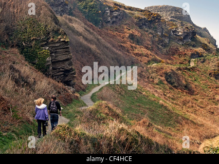 A couple walking along a path leading to Tintagel Castle on the rugged North Cornwall coast. Tintagel Castle is - Stock Photo