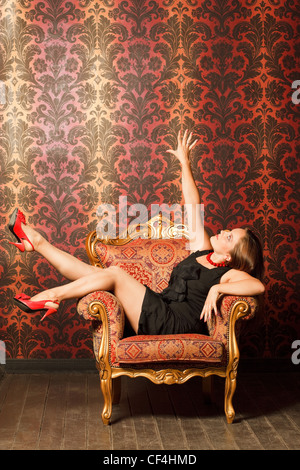 Woman in red shoes and a black dress sitting on a chair with a red-yellow wallpaper. hand is raised up. joy - Stock Photo