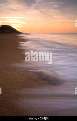The sun rises over Burton Bradstock on the Dorset Coast. - Stock Photo