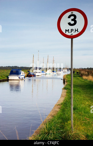 A 3 mh maximum speed limit sign on the Norfolk Broads with yachts moored in the background. - Stock Photo