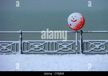 A smiley face drawn in the snow covering a red sign on the seafront at Brighton. - Stock Photo