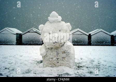 A snowman on Hove Lawns with snow covered beach huts in the background. - Stock Photo
