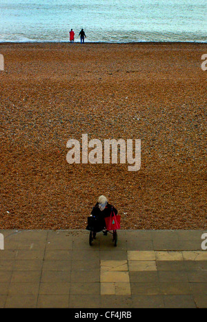 An elderly woman in a wheelchair by Brighton beach looking towards a young couple in the distance. - Stock Photo